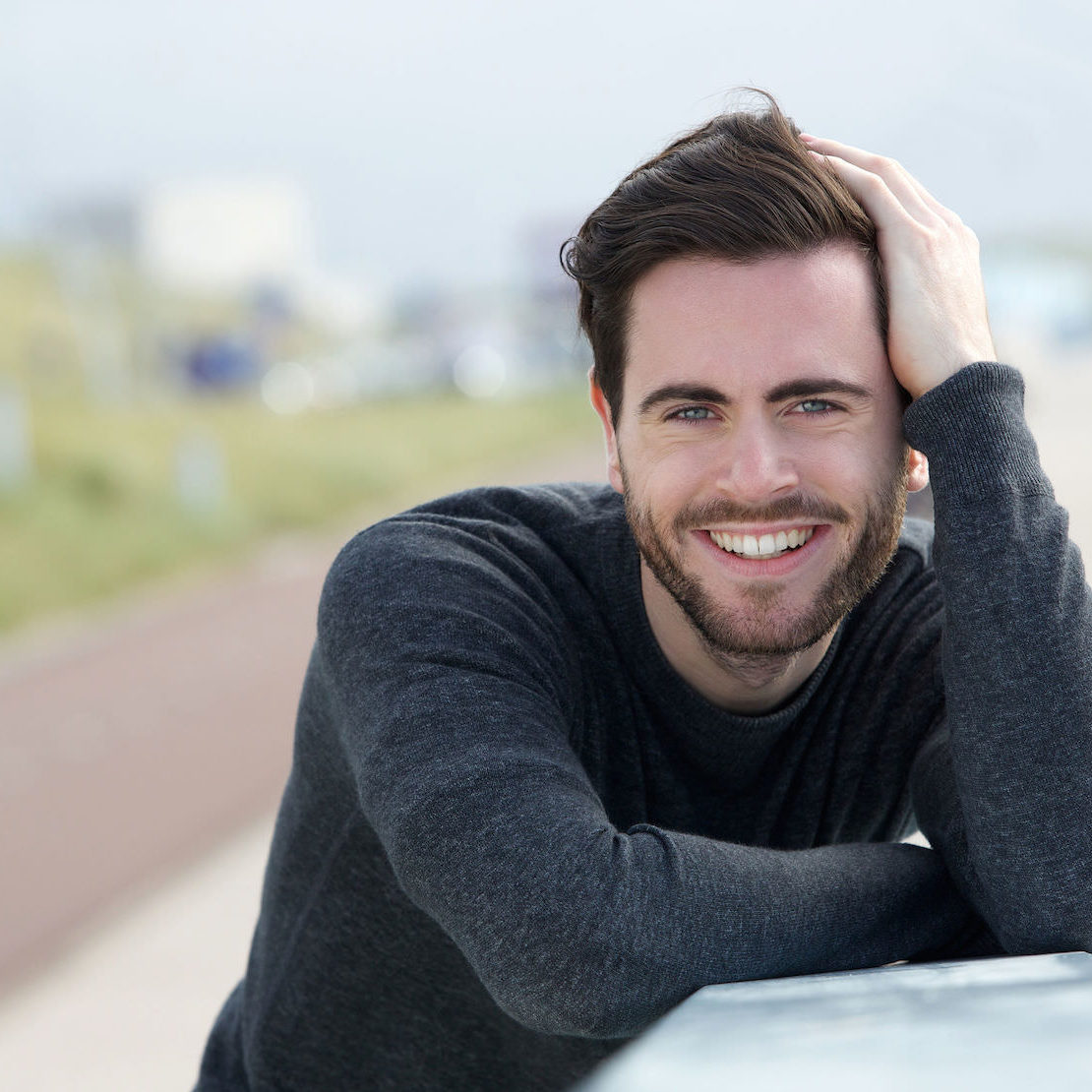 close up portrait of a happy man posing with hand in hair